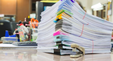 Image of examination booklets piled on a desk with colour coded corners